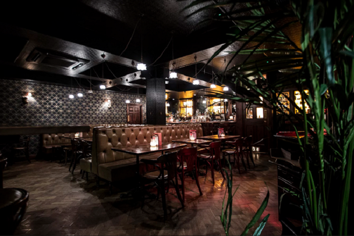 Dark interior decoration, low lighting and leather seating gives a luxury feel to one of the floors in the Cane & Grain secret bar in Manchester