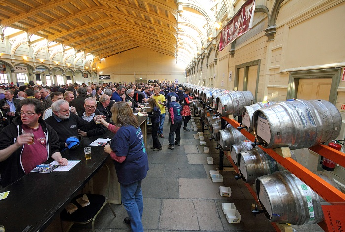 Festival goers sampling beers from a long row of kegs behind the bar at the Bristol Craft Beer Festival