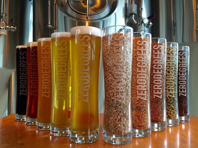 Five pints of lager from the Zero degrees bar in Bristol, lined up next to five pint glasses filled with ingredients including barley and wheat