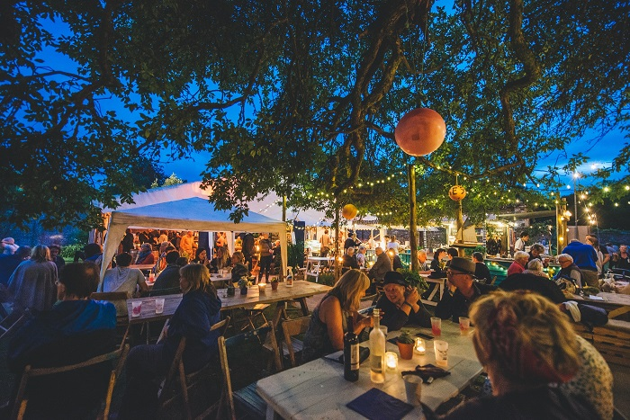 People sitting at open air tables surrounded by fairy lights and white tents at dusk at Port Eliot Festival, image credit – C Faruolo