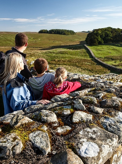 Family looking out over Housesteads Fort onto Hadrian's Wall