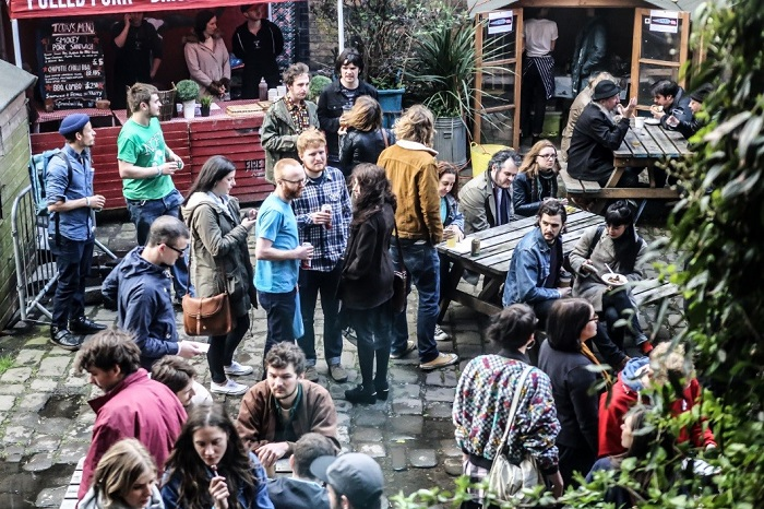 Young people drink and chat together in the outdoor beer garden of The Islington Mill bar in Manchester