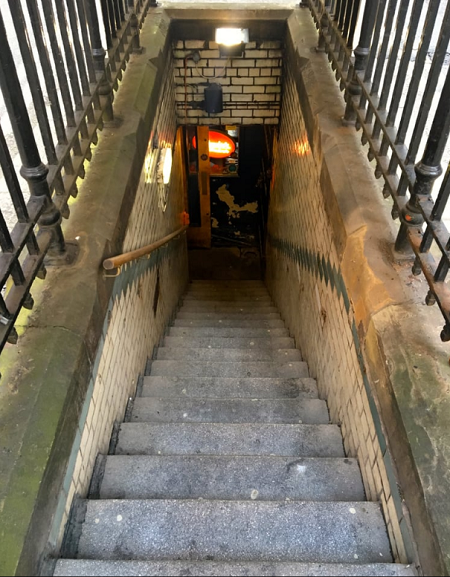 Concrete steps surrounded by meta railings lead down to the Temple bar in Manchester