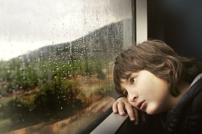 Bored child leans against a rainy train window
