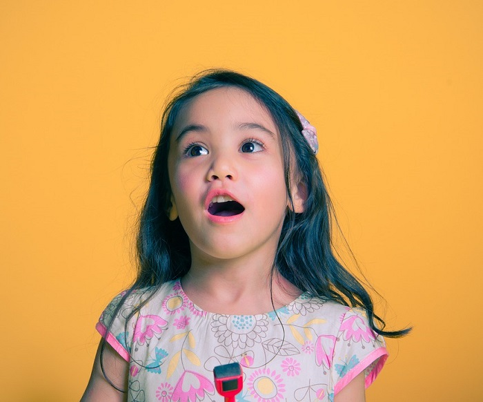 A little girl singing against a yellow background