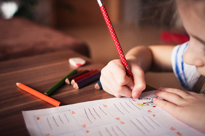 Child writing with a red pencil