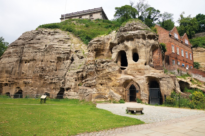 The exterior of Nottingham Castle on top of a hill surrounded by trees, with a smaller red brick building below next to some caves