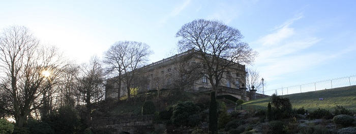 The exterior of the 17th century Nottingham Castle at dawn surrounded by bare trees and clear blue sky