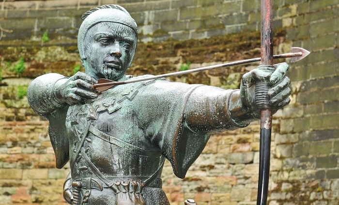 A bronze statue of Robin Hood stood ready to shoot his bow and arrow in a courtyard backed by a stone wall