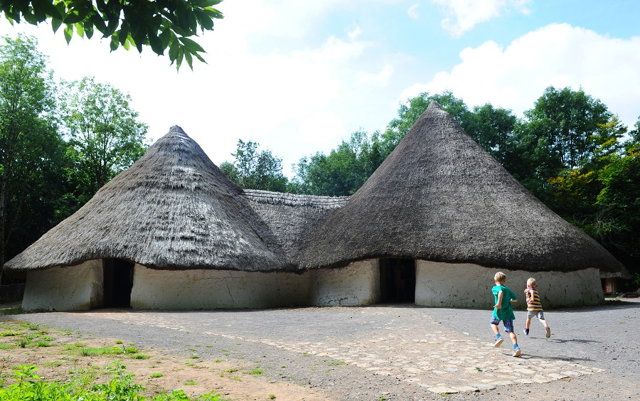 At St Fagans there is plenty of space to run around as well as learn, these children are running towards a reconstructed traditional welsh house with a thatched roof.
