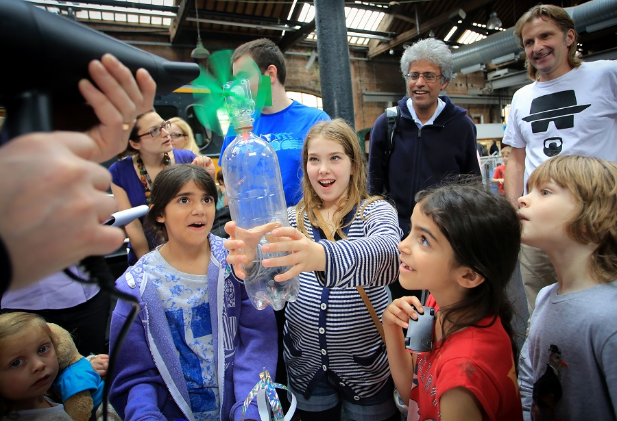 Here a group of fascinated and amazed children and their parents enjoy themselves partaking in a windmill experiment at The Museum of Science and Industry in Manchester