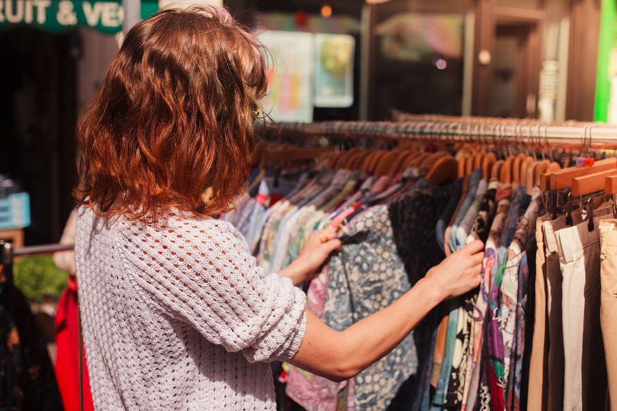 A woman browses the clothing rails of a vintage store