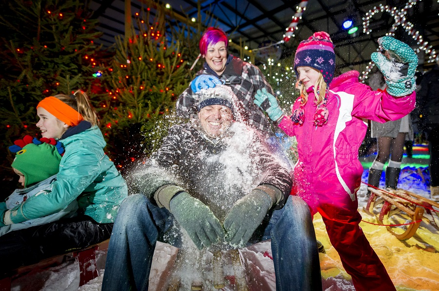 A little girl hits her Dad over the head with a snowball; Santa's Winter Wonderland is fun for all the family!