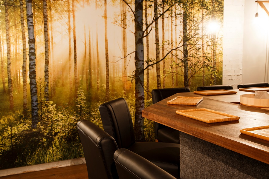 Inside the Smultronstalle restaurant with a high wooden table top accompanied by black leather stalls, five wooden serving mats and a wall sticker in the background featuring a sunshine-lit woodland