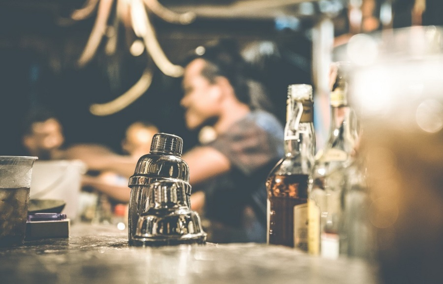 A barman in Birmingham's secret Speakeasy Bar with bottles of alcohol, 2 silver cocktail shakers and a glass of cocktail sat on the bar