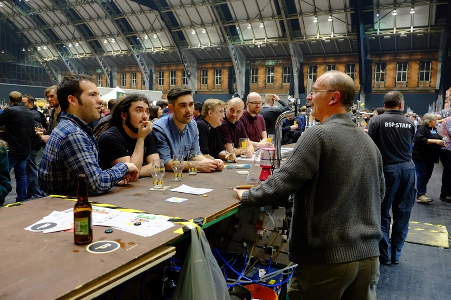Six men lean against a bar as they learn about the beer they're drinking in a tasting session at the festival.