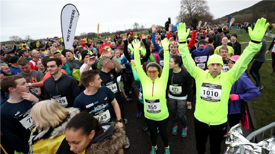 A large group of runners stand warming up at the start line of the Great Edinburgh Winter Run with their hands in the air