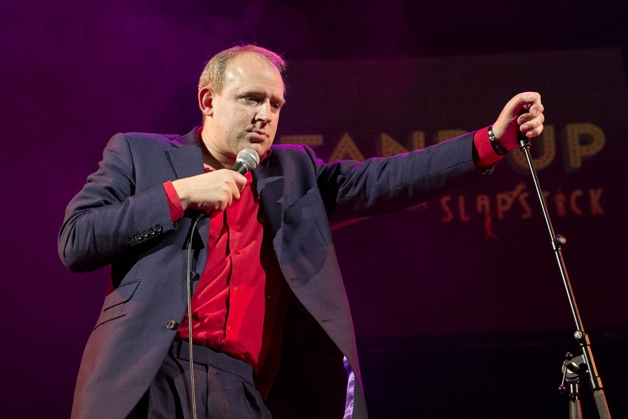 Comedian Tim Vine leans against his microphone stand as he takes the stage at Slapstick2017.