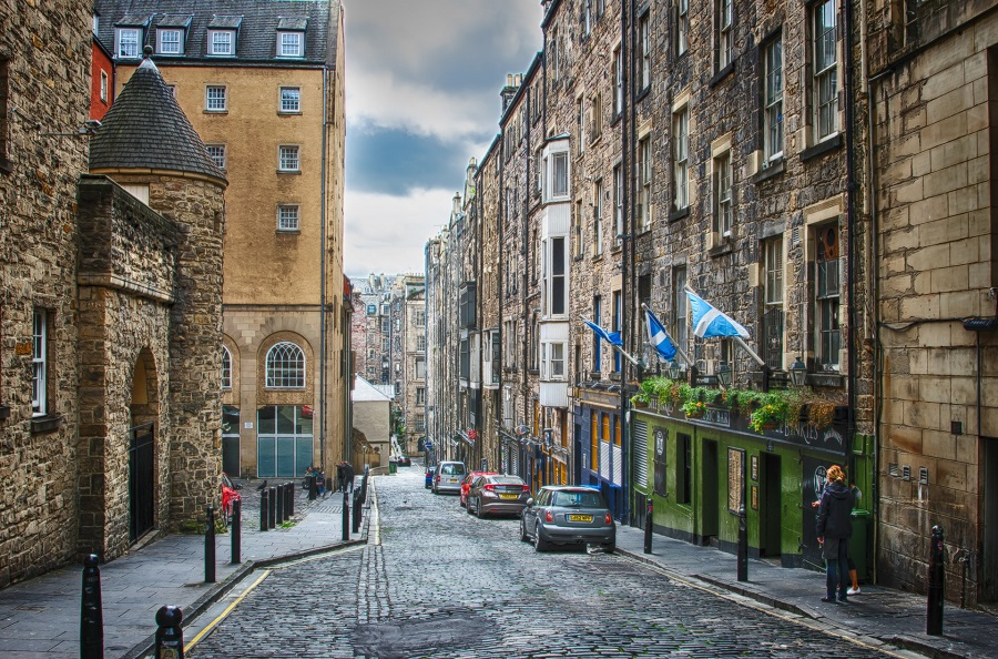 A street in Edinburgh with tall buildings either side, cars parked in the street and 3 Scottish flags flying outside a green pub