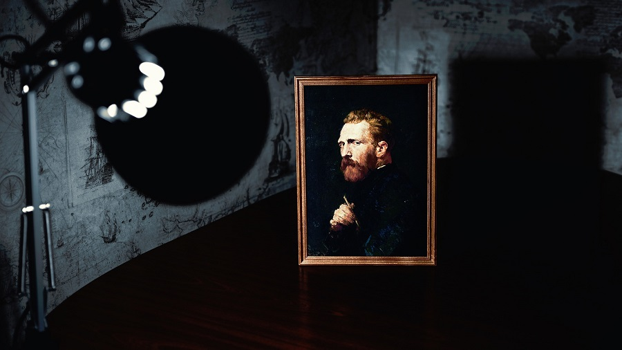 A lamp shining on a painting of Van Gogh in a dark room with graffiti on the white walls