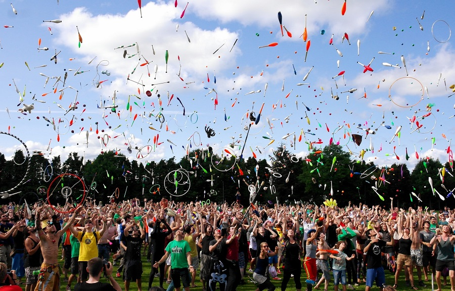 A large crowd of people partying in a field throwing colourful ribbons, streamers and juggling bats in the air