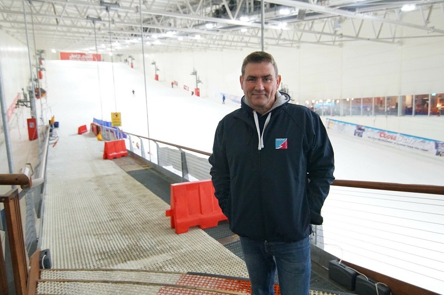 Smiling owner Jamie Smith in a blue jumper and jeans, standing in front of a ski slope covered in crisp white snow inside Ski Factor.