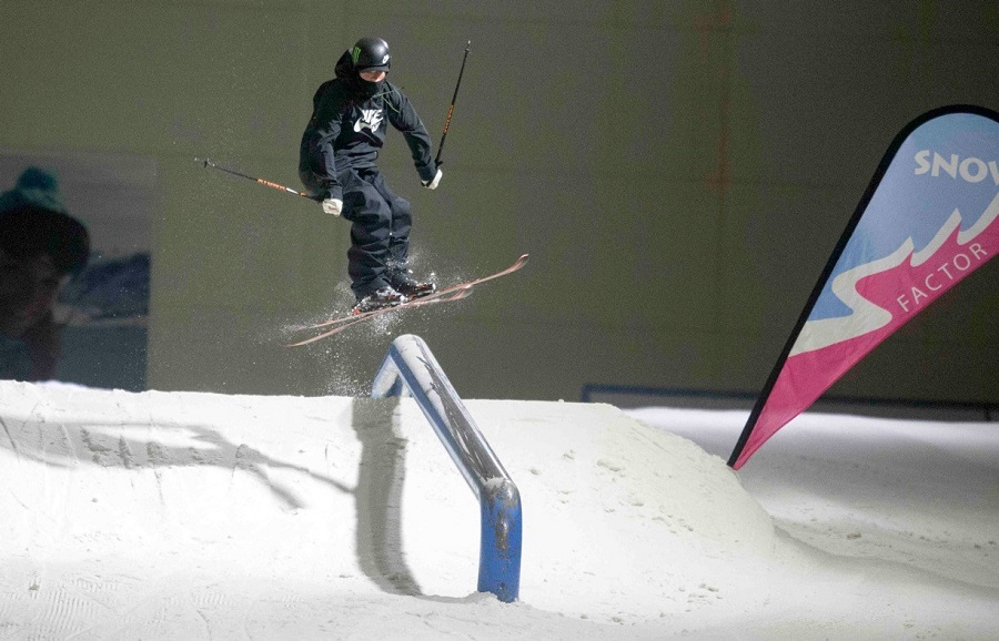 A skier in a black snowsuit doing a high jump on the indoor ski slopes at Snow Factor.  Caption: Photo Credit Jeff Holmes Photography