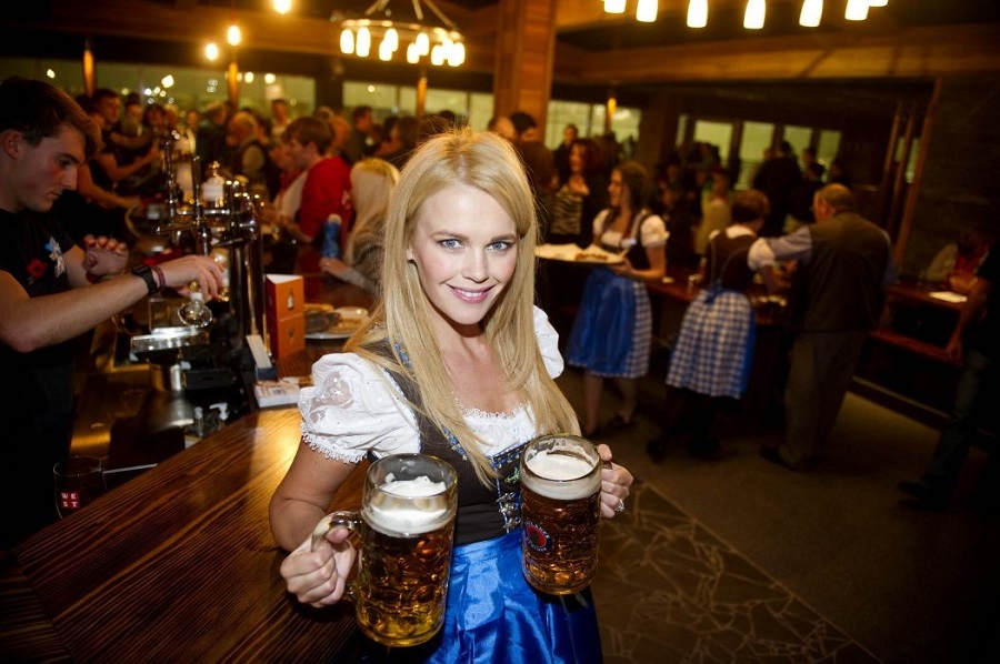 Smiling bar server dressed like an authentic Bavarian waitress with long blonde hair holding two large glasses of German beer in a busy bar Caption: Photo Credit Jeff Holmes Photography