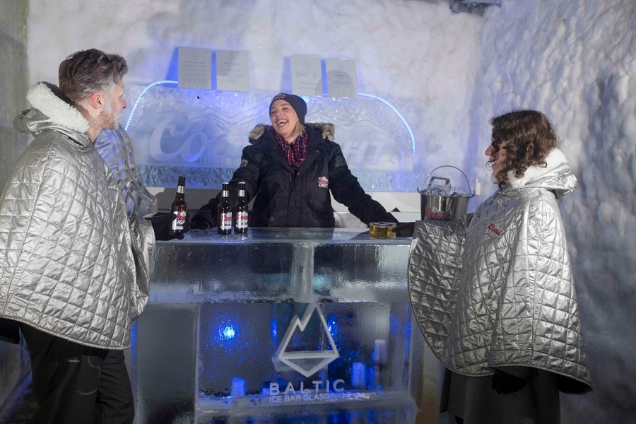 Three people wearing big winter coats drinking bottles of beer at a bar made from ice, surrounded by snow-covered walls  Caption: Photo Credit Jeff Holmes Photography