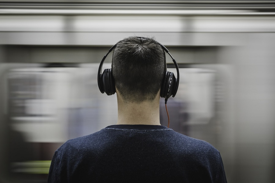 A man wearing a blue jumper, standing with his back to the camera listening to music on large headphones as a train rushes past