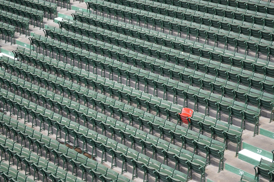Hundreds of green seats and a single red seat inside a large stadium