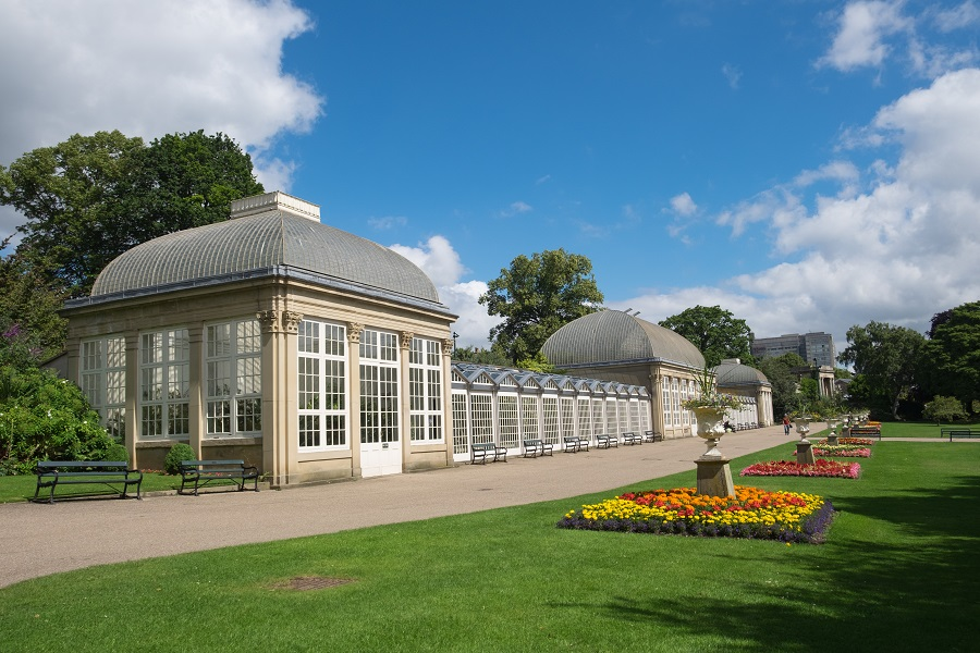 Sheffield Botanical Gardens Glasshouses are surrounded by green grass and colourful flowers