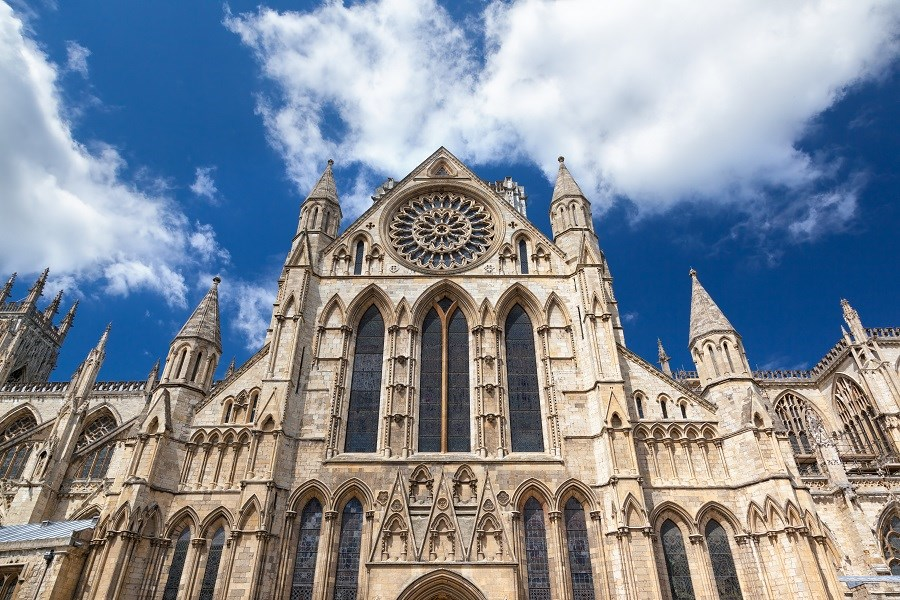 The front entranceway of the stunning regal York Minster building with a backdrop of blue skies and fluffy white clouds is the perfect place to visit this Valentines Day.
