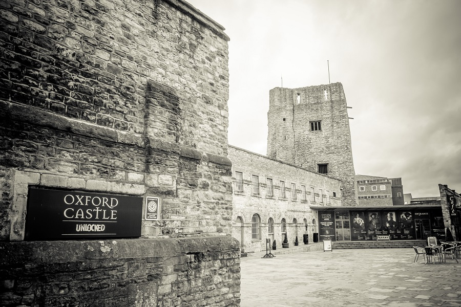 Cobbled buildings with barred windows surround a square with tables and chairs. A sign reading Oxford Castle unlocked is hung on one of the walls