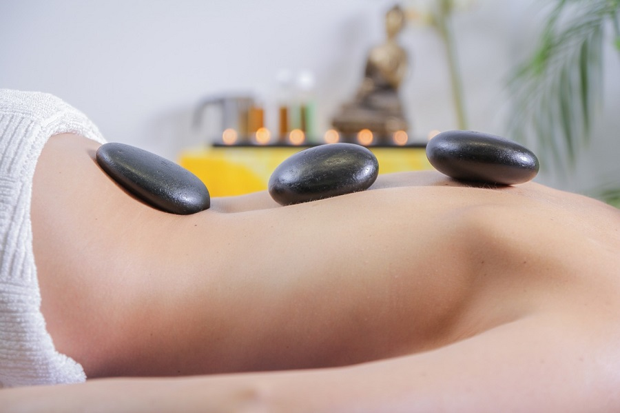 A woman wearing a white towel laying on her front with three black stones on her spine in a massage room with a green plant, massage oils and a Buddha statue in the background
