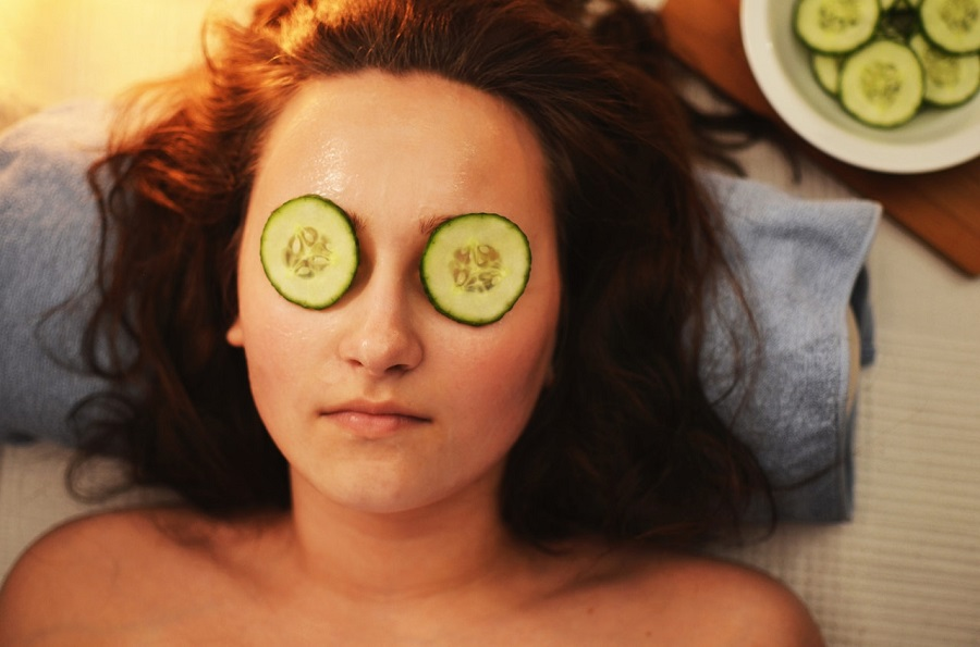 A woman with brown hair laying on a blue pillow with cucumber slices on her eyes looking relaxed