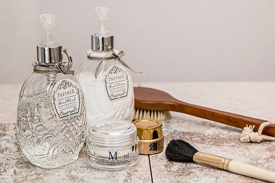 1 glass bottle filled with white lotion stood next to another glass bottle filled with oil, a makeup brush, a wooden loafer brush, and 2 small pots of makeup sat on a marble surface