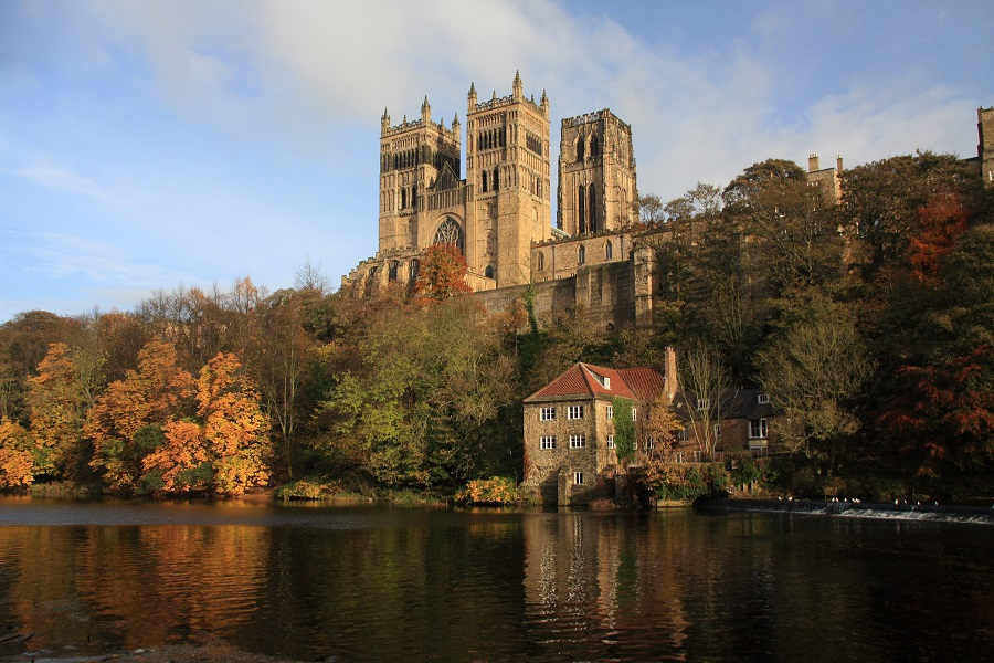 A gorgeous honey-coloured stone cathedral sits above a peaceful river surrounded by autumnal trees