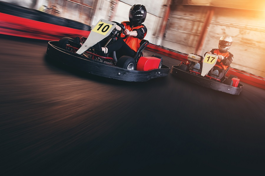 Two people race go karts on an indoor track