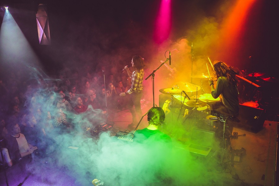 A band playing a keyboard, a set of drums and singing on a stage in front of a crowd, with colourful strobe lights and smoke