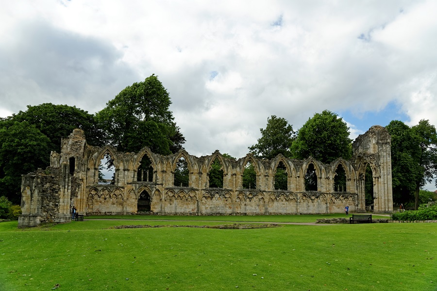 Medieval ruins of St. Mary's Abbey in York Museum Gardens sit on green grass