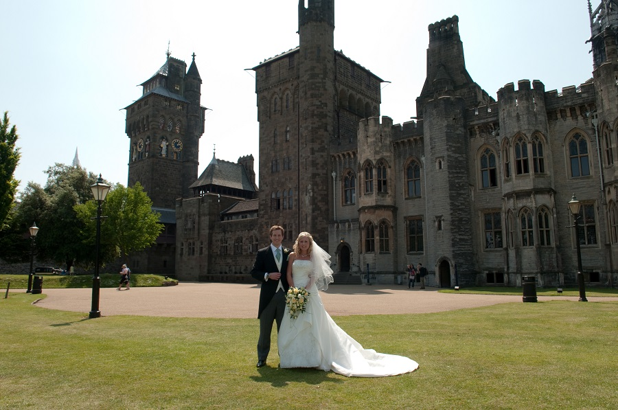 A newlywed couple standing on a green lawn in front of the grand exterior of Cardiff Castle .
