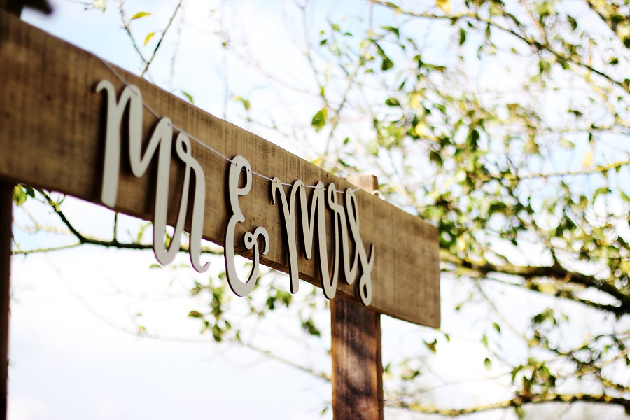 A closeup of an outdoor wooden sign with a hanging metal sign that reads: Mr & Mrs with a green tree in the background