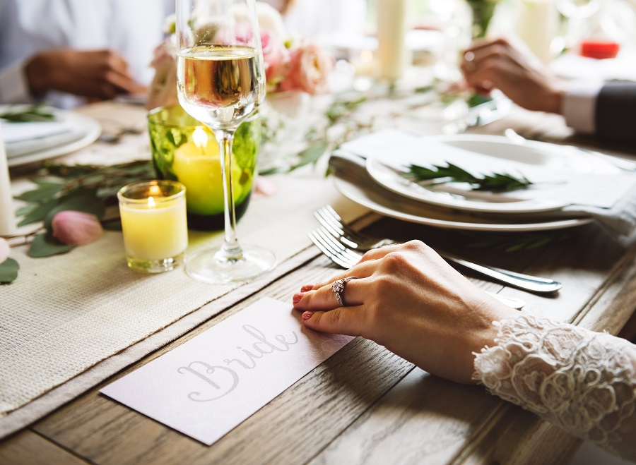 A closeup of a bride's hand on a wooden table filled with plates, candles, flowers and a glass of white wine surrounded by guests.