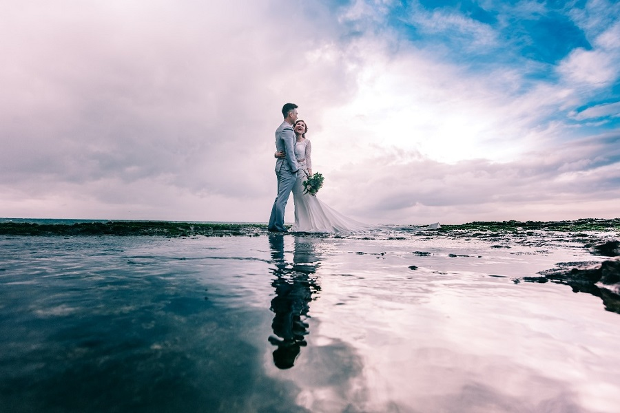 Smiling newlywed couple standing on the shoreline together with the sun reflecting off the sea