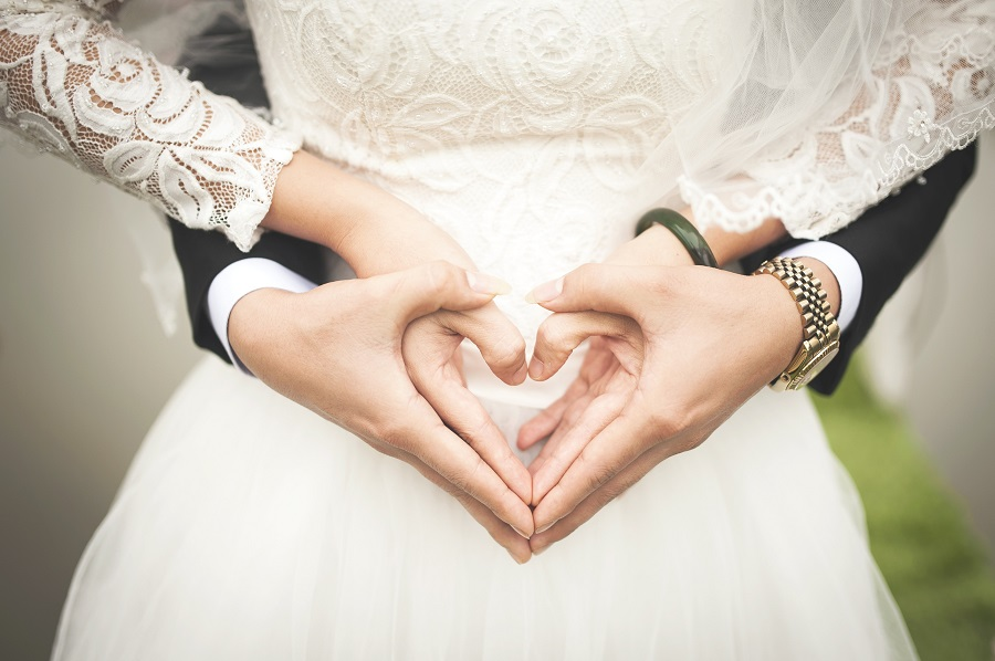 A close-up of a bride in a classic wedding dress and a groom using their hands to make two love hearts