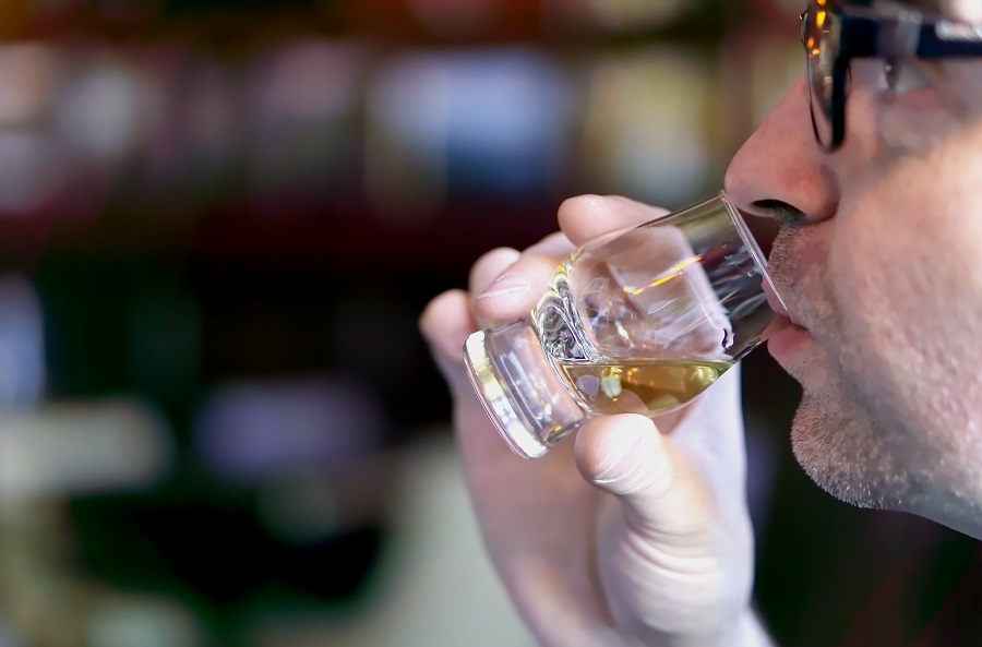 Man wearing glasses tasting whisky from a sample glass in Scotland.