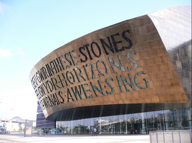 Wales Millennium Centre glass building which is coloured at the front and has letters engraved on it.