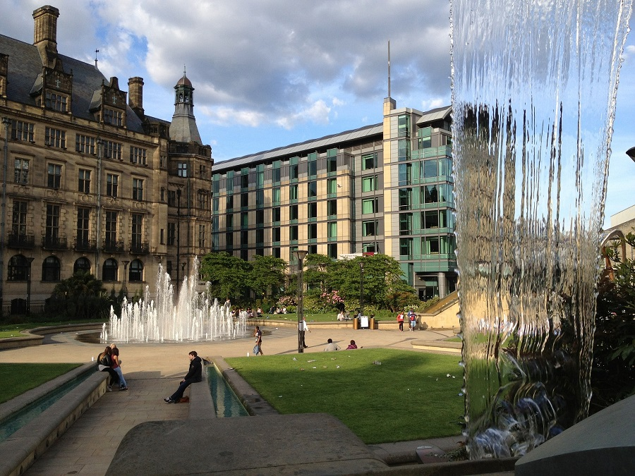 Water fountains flow in a square of grassy areas in Sheffield's Peace Gardens