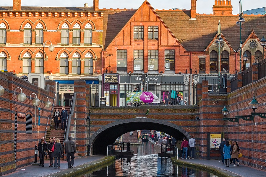 Pedestrians walk either side of a canal flowing under a bridge in Birmingham city centre.